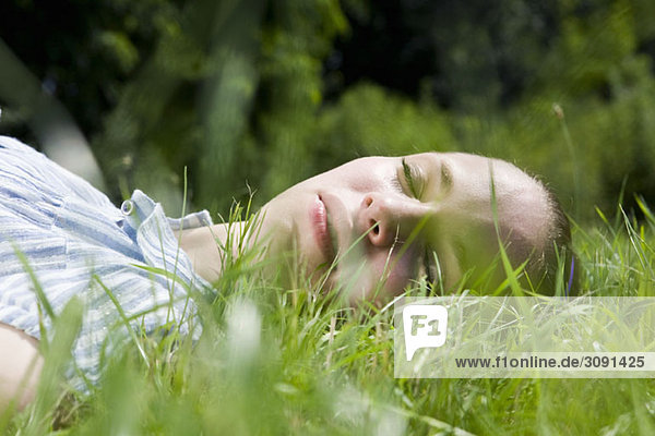 A young woman lying in grass sleeping