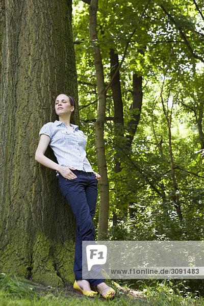 Eine junge Frau  die sich an einen Baum lehnt.