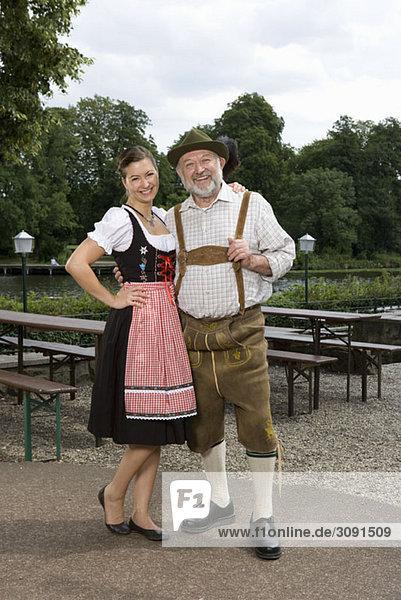 Ein traditionell gekleideter deutscher Mann und Frau in einem Biergarten