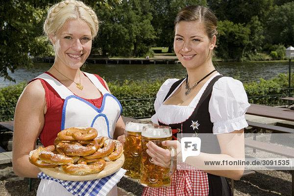 Zwei traditionell gekleidete deutsche Frauen servieren Brezeln und Bier in einem Biergarten.