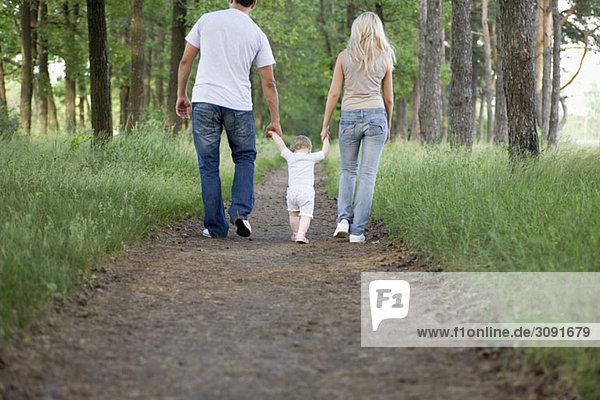 Zwei Eltern  die mit ihrer kleinen Tochter auf einem Waldweg spazieren gehen.
