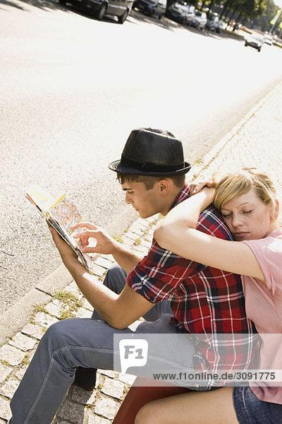 Ein junges Paar mit Koffer und Karte