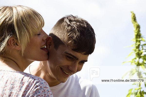 Eine junge Frau leckt einem jungen Mann spielerisch das Ohr.