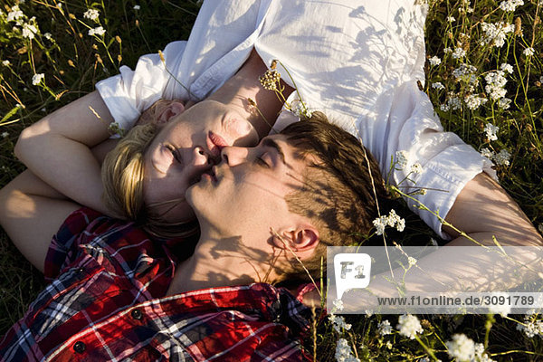 Ein junges Paar schlafend auf einem Feld