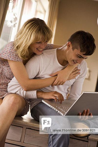 Ein junges Paar mit einem Laptop zusammen