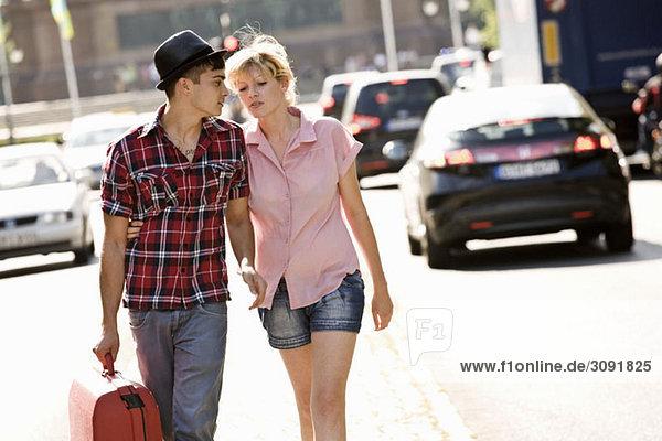 Ein junges Paar  das mit einem Koffer geht.