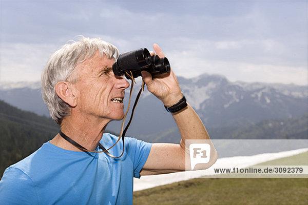 Senior mit Fernglas in den Bergen