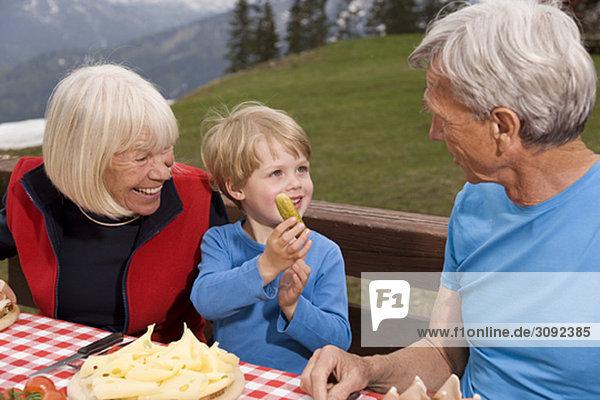 Paar und Enkel beim Essen in den Bergen