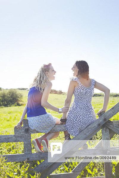 zwei Mädchen auf einem Zaun sitzend