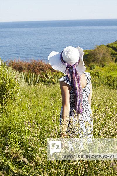 Ein Mädchen auf einem Feld  das auf das Meer schaut.