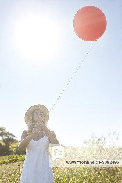 Ein Mädchen auf einem Feld mit einem roten Ballon