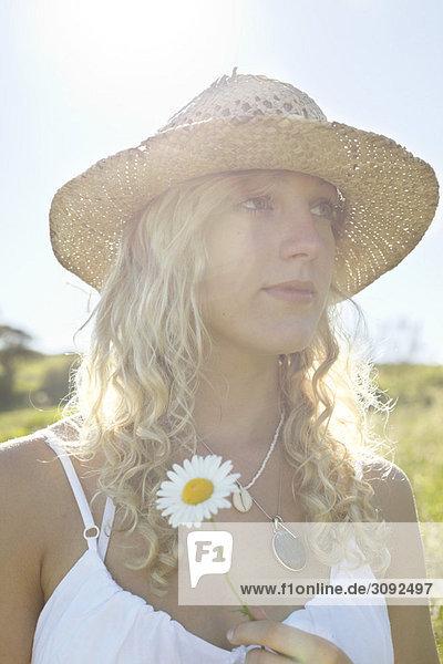 Ein Mädchen auf einem Feld mit einer Blume.