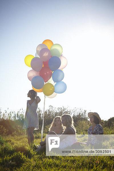vier Mädchen auf einem Feld mit Luftballons