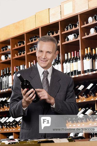 Unternehmer hält eine Weinflasche