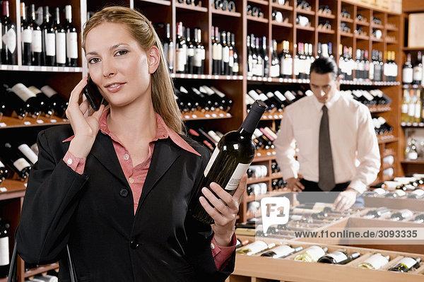 Geschäftsfrau Gespräch auf einem Mobiltelefon und eine Weinflasche hält
