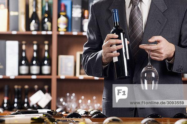 Unternehmer hält ein Glas Wein und eine Weinflasche