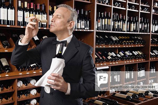 Kellner riechen Cork einer Weinflasche