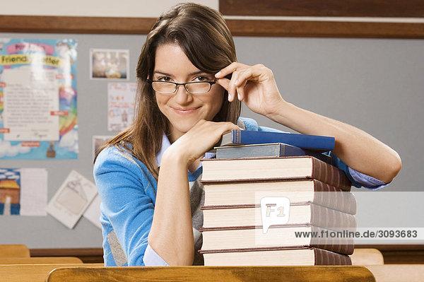 Portrait eines Lehrers mit einem Stapel von Büchern in einem Klassenzimmer
