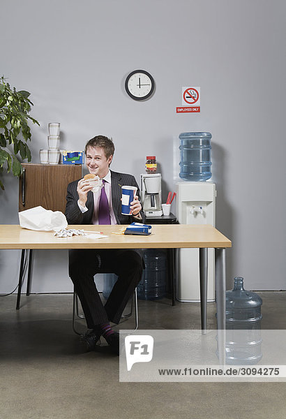 Kaufmann mit Mittagessen im Büro
