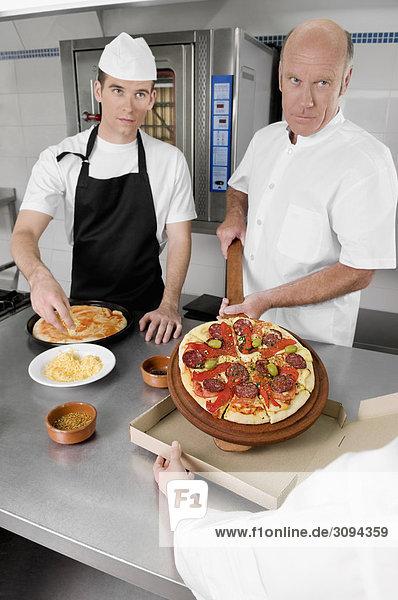 Drei Chefs Pizza in der Küche vorbereiten