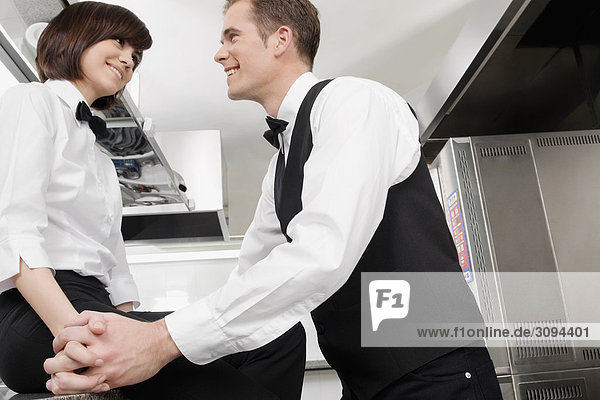 Kellner und Kellnerin romancing in der Küche