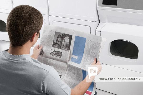 Mann lesen eine Zeitung in ein Waschsalon