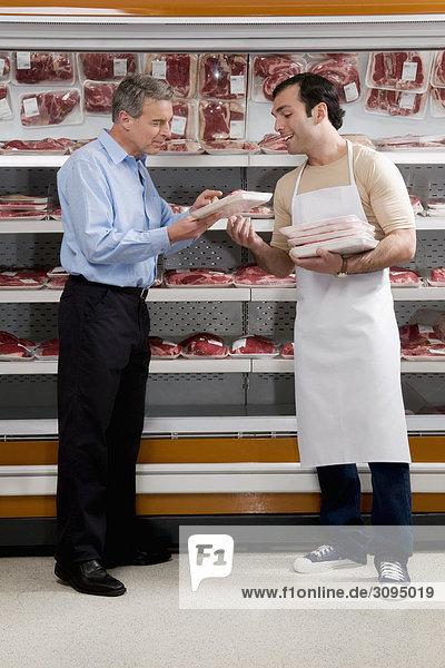 Verkaufssekretärin unterstützen einen Kunden auswählen Fleisch in einen Supermarkt