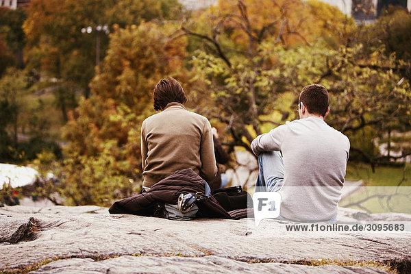 Rückansicht eines Mannes und einer Frau sitzend auf einem Felsen in einen Park  New York City  New York State  USA
