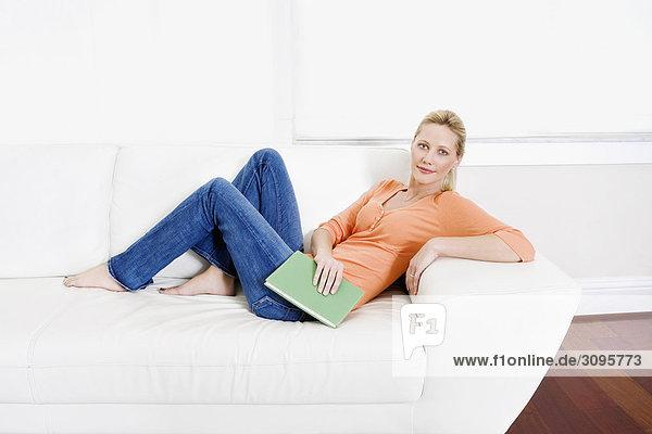 liegend liegen liegt liegendes liegender liegende daliegen Frau Buch halten Couch Taschenbuch zurücklehnen