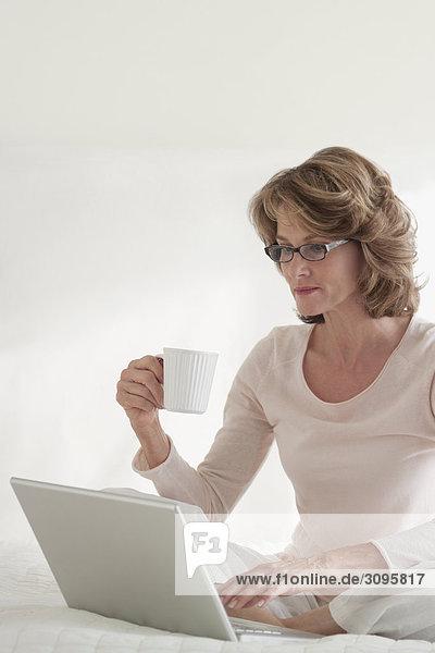 Frau Notebook arbeiten Bett