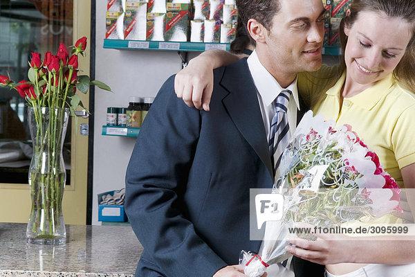 Paar hält ein Blumenstrauß in ein Blumengeschäft