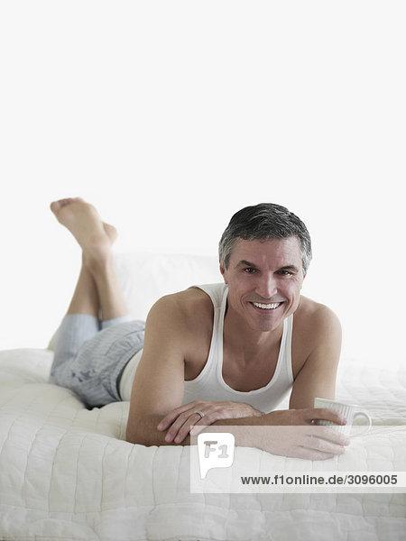 liegend liegen liegt liegendes liegender liegende daliegen Mann Tasse lächeln halten Bett Kaffee