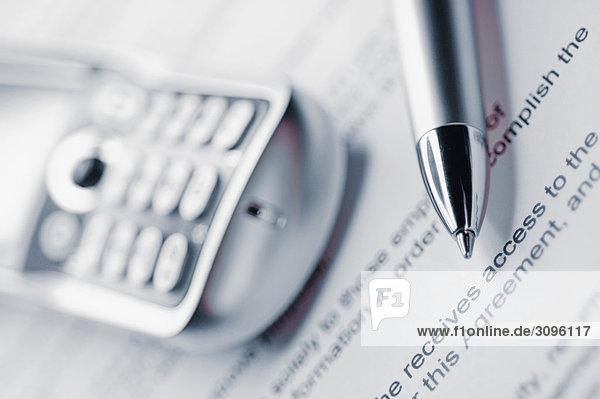 Nahaufnahme eines Mobiltelefons mit einem Stift auf einem Blatt Papier