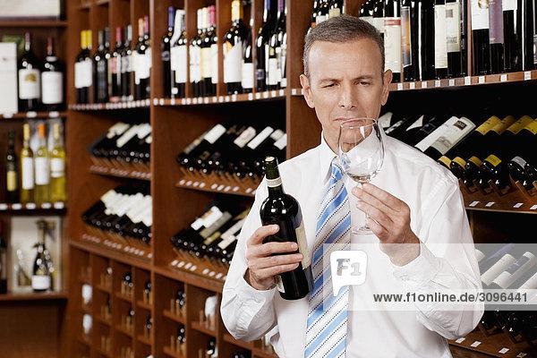 Unternehmer hält ein leeres Glas Wein mit einer Weinflasche