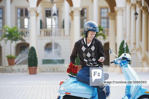Man sitzt auf einem Moped und Text-messaging auf ein Handy  Biltmore Hotel  Coral Gables  Florida  USA