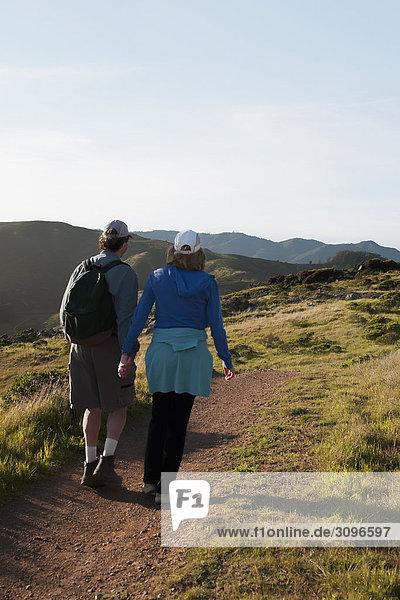 Rückansicht eines Paares zu Fuß auf einem Wanderweg