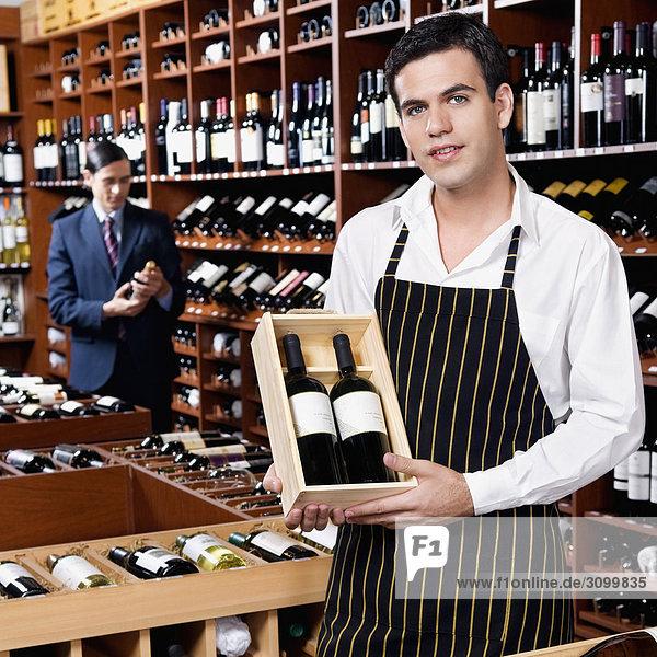 Verkaufssekretärin zeigt eine Kiste Weinflaschen