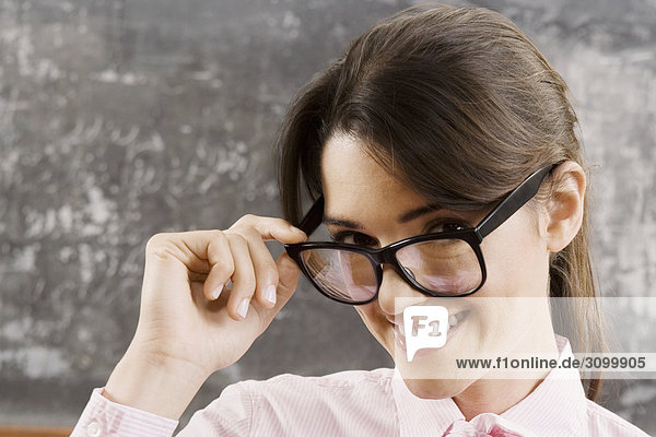 Female teacher looking over her eyeglasses and smiling