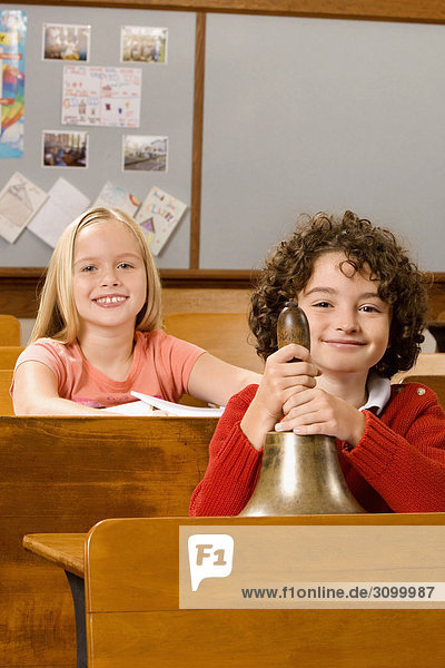 Schoolboy holding a bell with a schoolgirl sitting behind him in a classroom