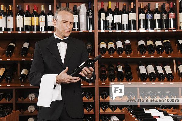 Kellner lesen die Bezeichnung einer Weinflasche