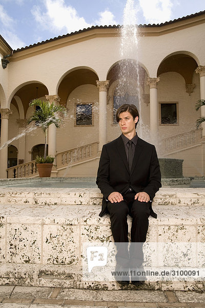 Businessman sitting in der Nähe von einem Brunnen  Biltmore Hotel  Coral Gables  Florida  USA