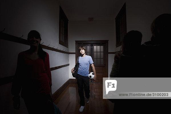 Teenager mit einen Fußball Ball im Korridor Schule