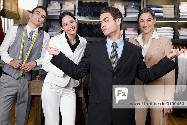 Portrait eines Kaufmanns mit zwei Verkäuferinnen und Schneider in einem Speicher