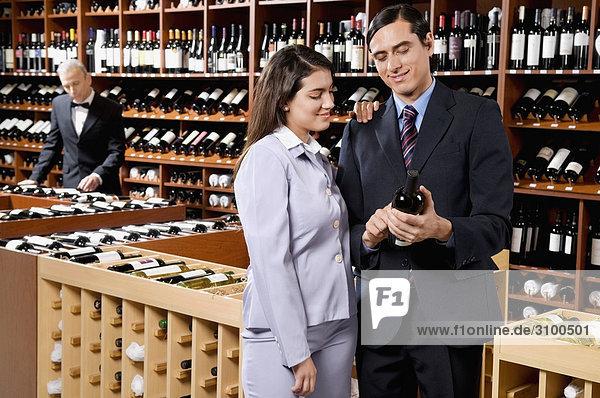 Paar lesen die Bezeichnung einer Weinflasche in einer bar
