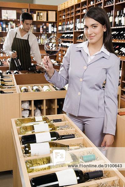 Geschäftsfrau hält ein Glas Wein in einer Bar und lächelnd