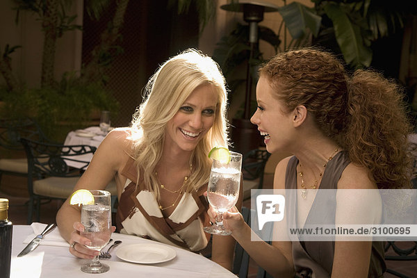 Two women smiling and holding drinks in a hotel  Biltmore Hotel  Coral Gables  Florida  USA