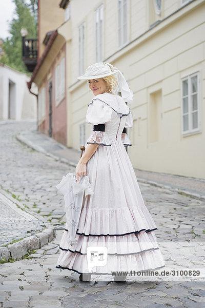 Portrait einer Frau stehend auf einer Straße und lächelnd