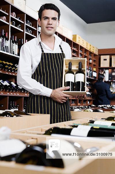 Verkaufssekretärin halten eine Kiste Weinflaschen
