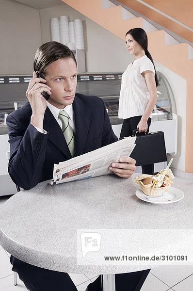 Geschäftsmann auf einem Mobiltelefon in einer Eisdiele sprechen