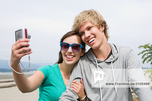 Teenage couple with digital camera